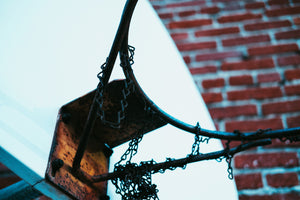 Close Up of Basketball Hoop with a Rusted Chain Against a Brick Wall In Los Angeles