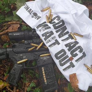 Contact Wait Out Tshirt laid over an AR15 rifle and scattered spent ammunition