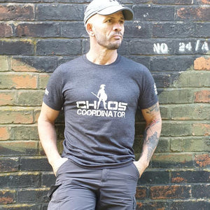 Craig Dean wearing the Chaos Coordinator tshirt while leaning back against a wall