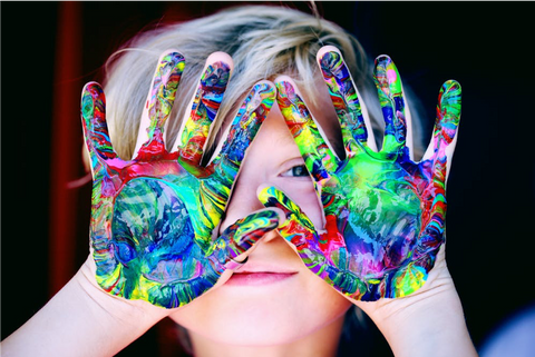 Image of child with paint on his hand looking happy