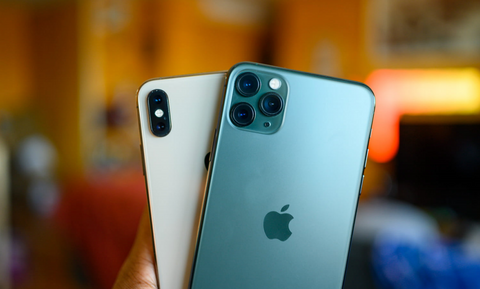 Image of two iPhones being held in the hand of a person with blurry background