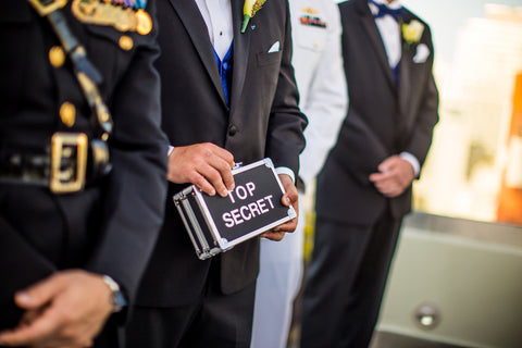 Image of Military officials standing in line and holding a top secret briefcase