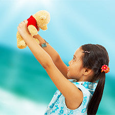 Girl holding her stuffed animal up in the air and smiling.