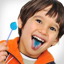 Little boy eating a sucker and showing off his blue tongue.