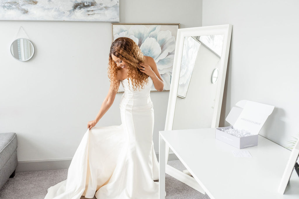 Bride trying on wedding dresses at home with Luxe in a Box