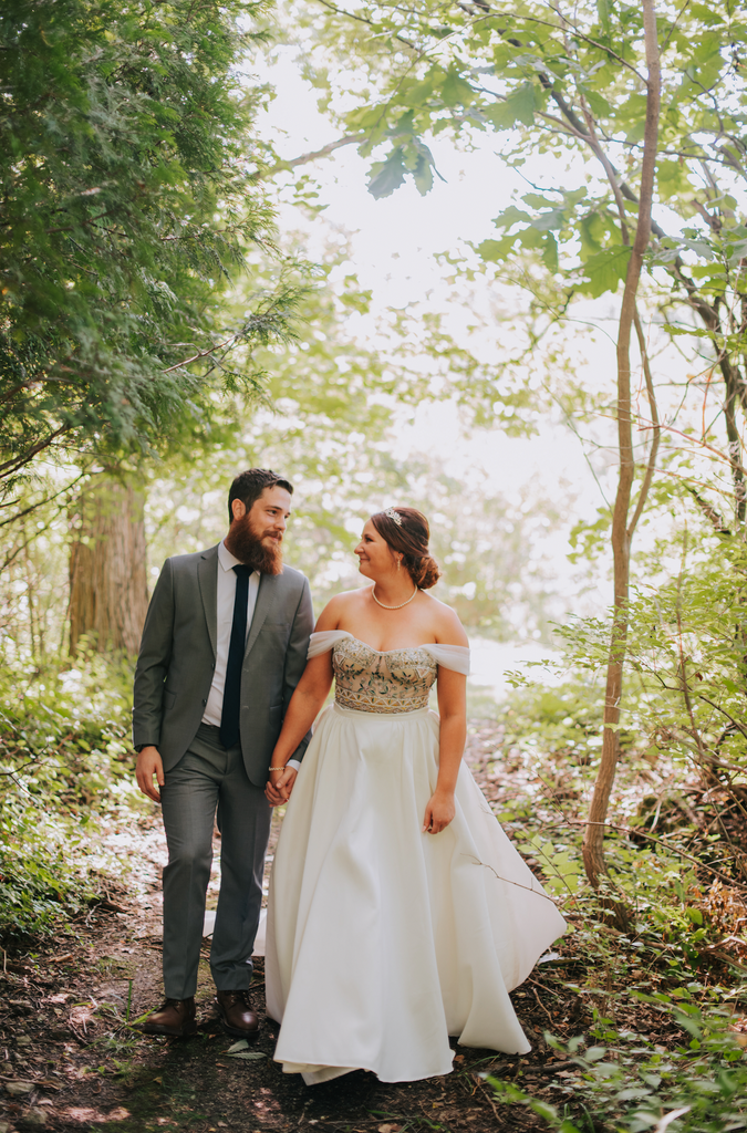 Bride and groom walking through trees for bridal portraits.