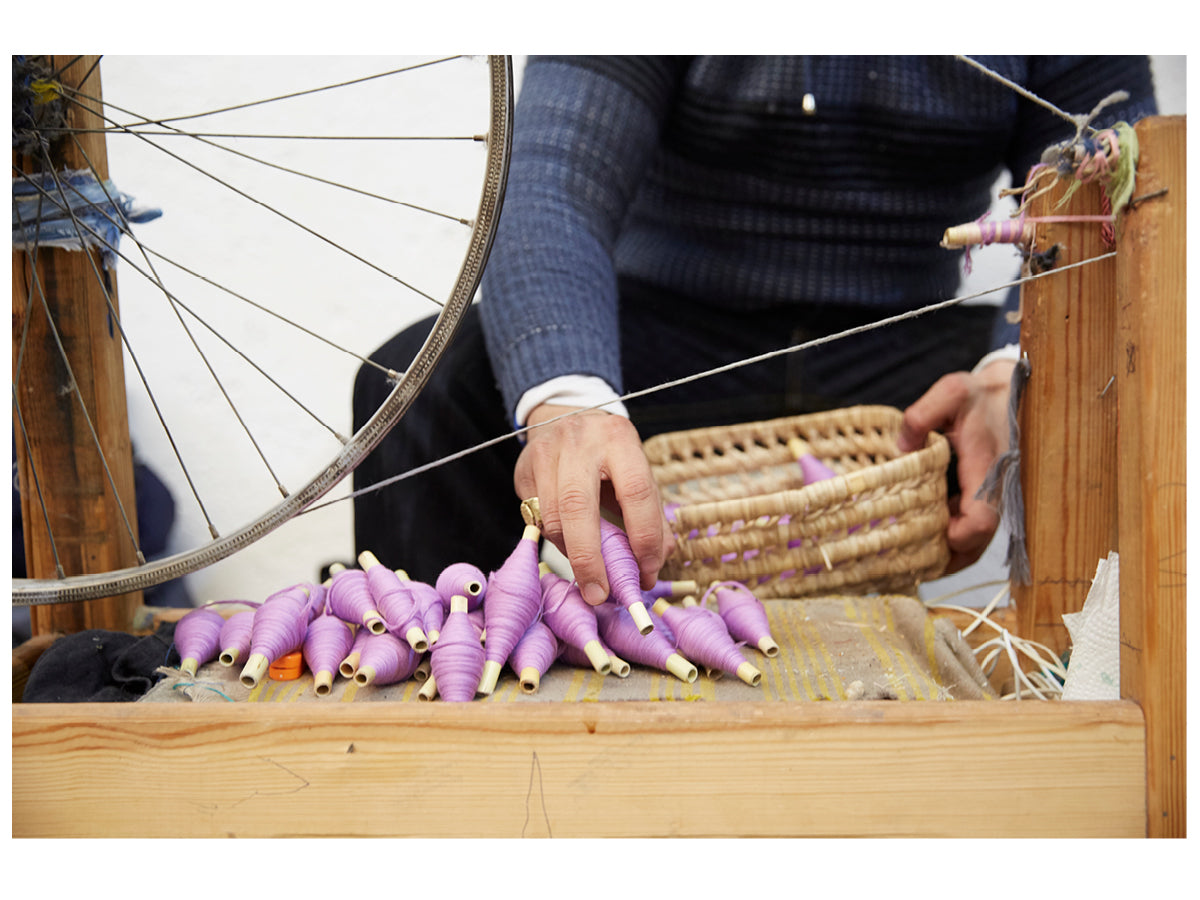 Image of an artisan sitting at a weaving loom and holding a basket of violet colored yarn spools.