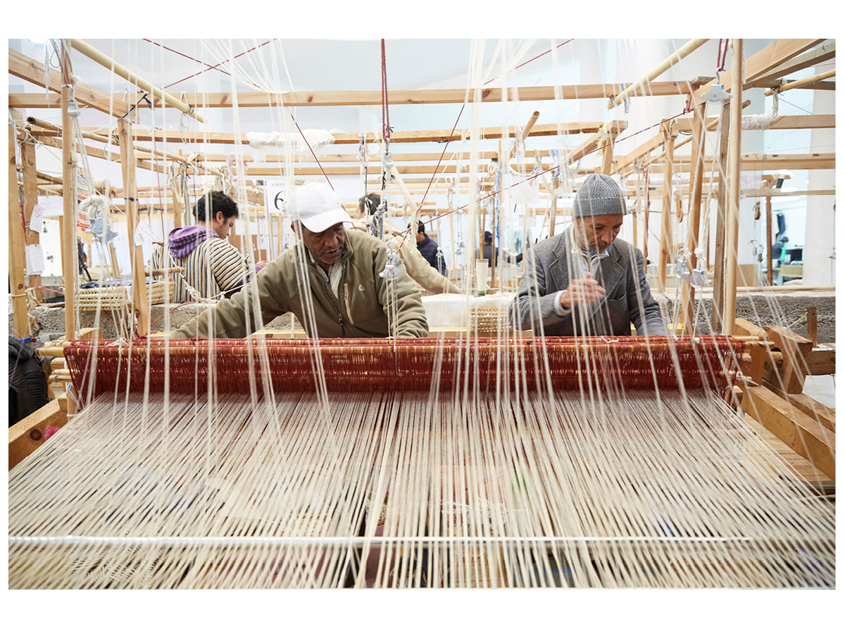 This image shows two male artisans working together at a large weaving loom in the Marrakshi Life atelier.
