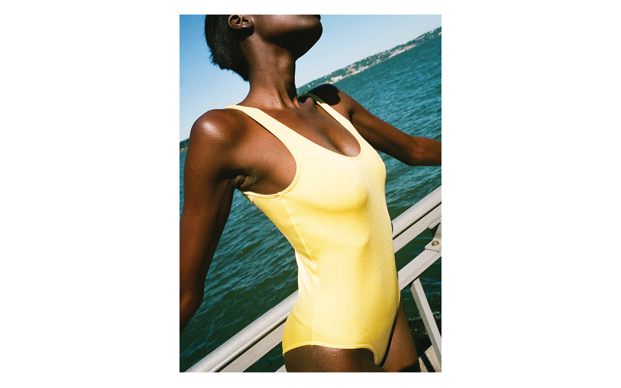 Image is of a woman wearing a yellow Baserange one piece Swimsuit.