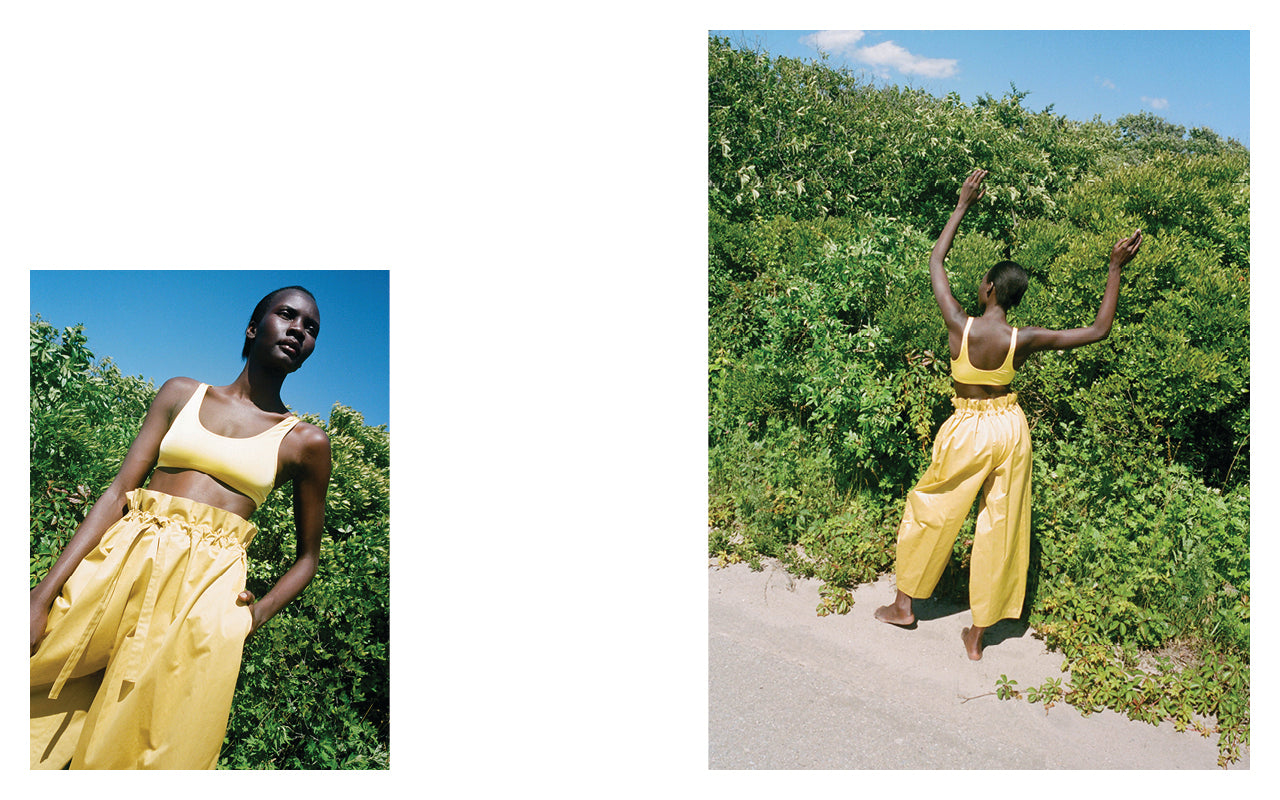 In both images a woman wears a Yellow bikini top by Baserange and pants by NEHERA