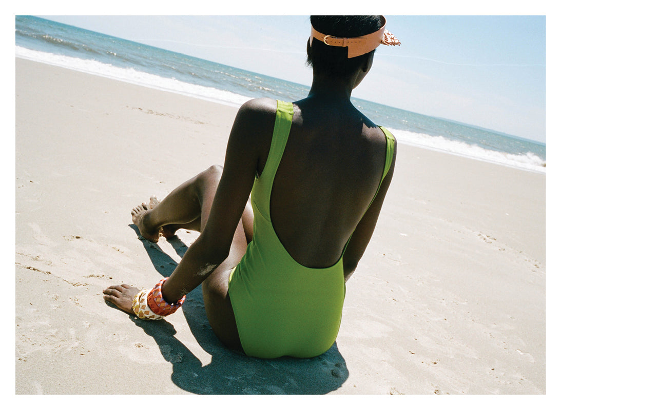 Image of a woman sitting on the beach wearing a Green one pice Swimsuit by Nu Swim with bangles and a visor by Hatori.