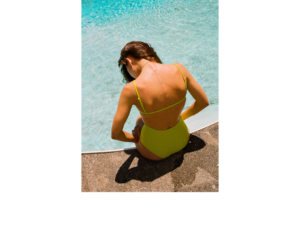 Image is of a woman sitting poolside with her back to the camera and wearing a Nu Swim bikini.