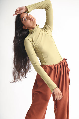 Baserange Omato Turtleneck in Topa Green on model view front