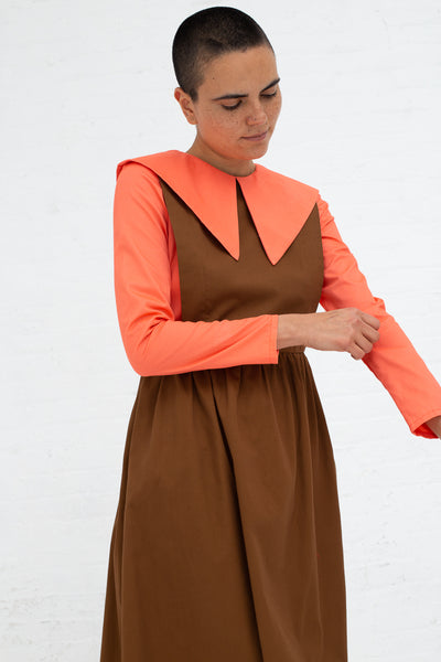 Batsheva Renaissance Dress in Coral and Brown, Front View Model Pulling Sleeve Up