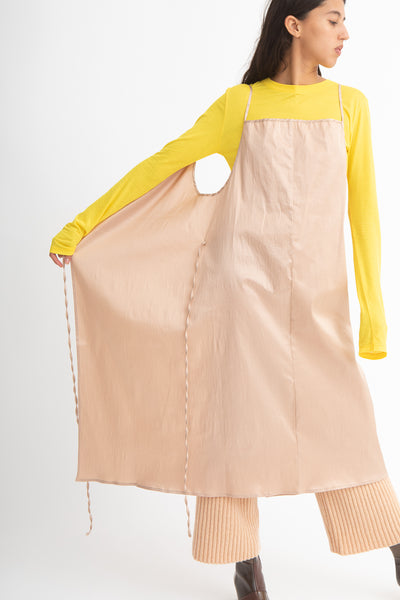 Baserange Yumi Apron Dress in Gravel Beige Front View Hand Pulling Skirt Out, Oroboro Store, New York, NY