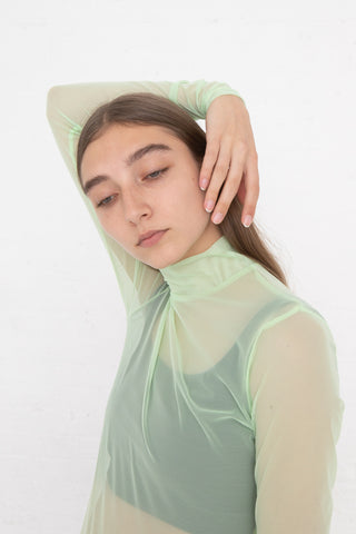 Nomia Long Sleeve Mockneck in Mesh Lime, Front View Arm Over Head, Oroboro Store, New York, NY