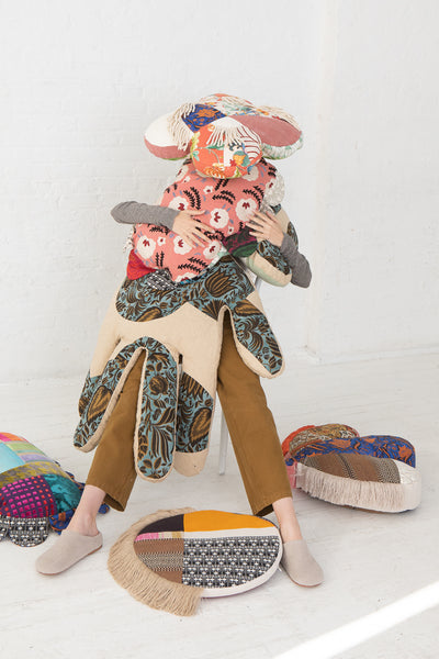 Wiener Times WW Travel Pillow in Drummerboy and Muilticolor, Cushions stacked on and around model sitting on chair