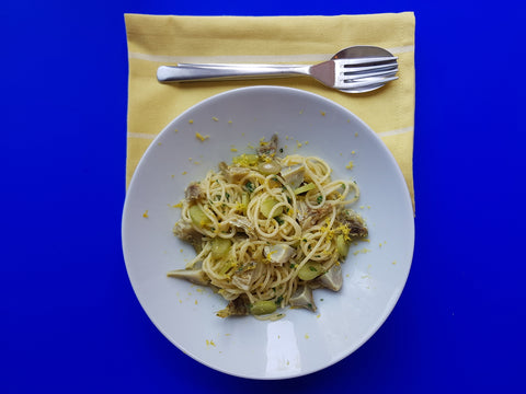 A plate of lemony artichoke pasta in front of a blue background