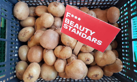"A box filled with kiwis, and a sign saying ""Fuck beauty standards"""