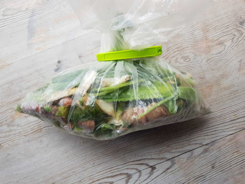 A plastic bag filled with leftover and cutoffs from veggies