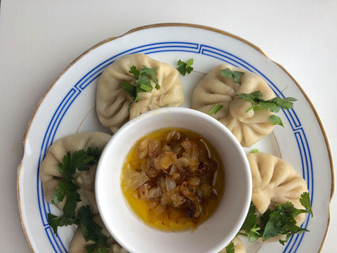 Serving of khinkali dumplings with a bowl of dip in the middle
