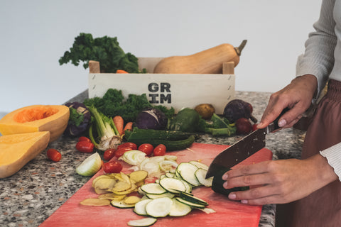 A person chopping different vegetables at a cutting board, in front of a GRIM veggie box