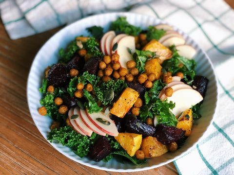 A bowl of kale salad with apples and pumpkin