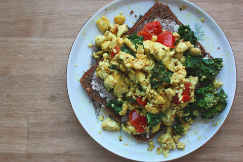 A slice of rye bread on a plate, topped with scrambled tofu and green kale
