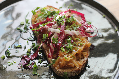 A slice of bread served with onion compote and a light salad