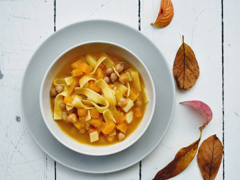 A bowl of butternut, chickpea and potato soup, next to some autumn leaves