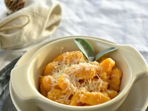 Pumpkin gnocchi with basil leaves served in a bowl