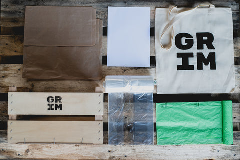 Image of GRIM packaging. A wooden box, bio-degradable plastic bags a tote bag etc.