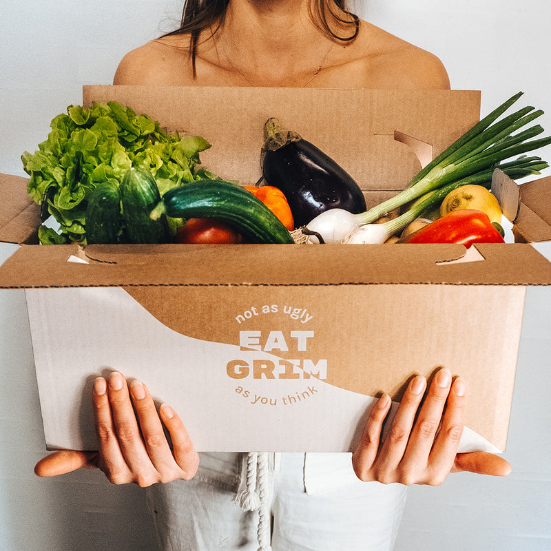 A person holding an open GRIM box, full of veggies
