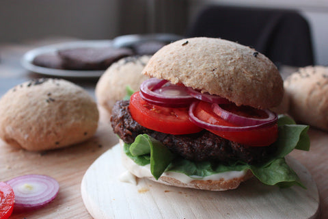 A vegan burger with different veggies, in front of some burger buns