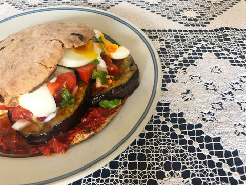 Pita burger filled with eggplant, eggs and different veggies on a plate