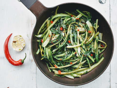 A cast iron pan with sauteed chicory, chili and garlic