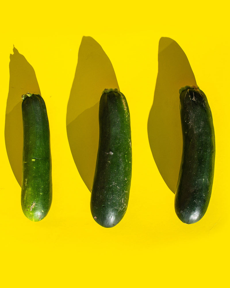 Three courgettes on a yellow background