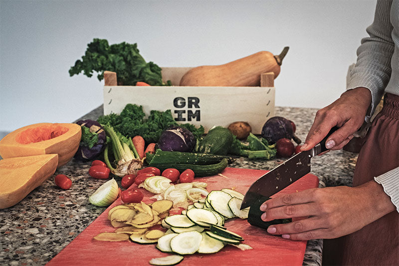 A person slicing a GRIM zucchini on a counter.