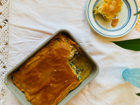 A pan filled with Spanakopita, next to a plate with a single slice