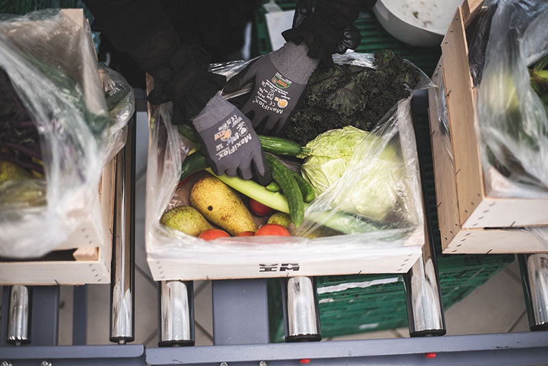 A GRIM vegetable box being packed by a person wearing gloves.