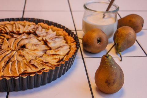 A pear tart served on a table next to fresh pears