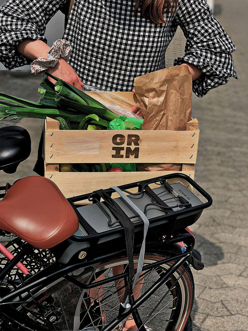 A person putting their GRIM vegetable box on the back of their bicycle.