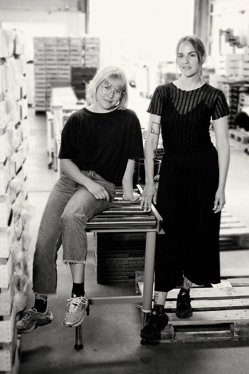 Two female founders of GRIM standing in their warehouse
