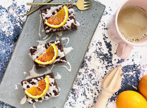 A serving slate with three slices of sweet potato brownies, topped with blood orange slices