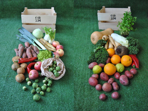 Two different GRIM veggie boxes with the produce spread out across the floor
