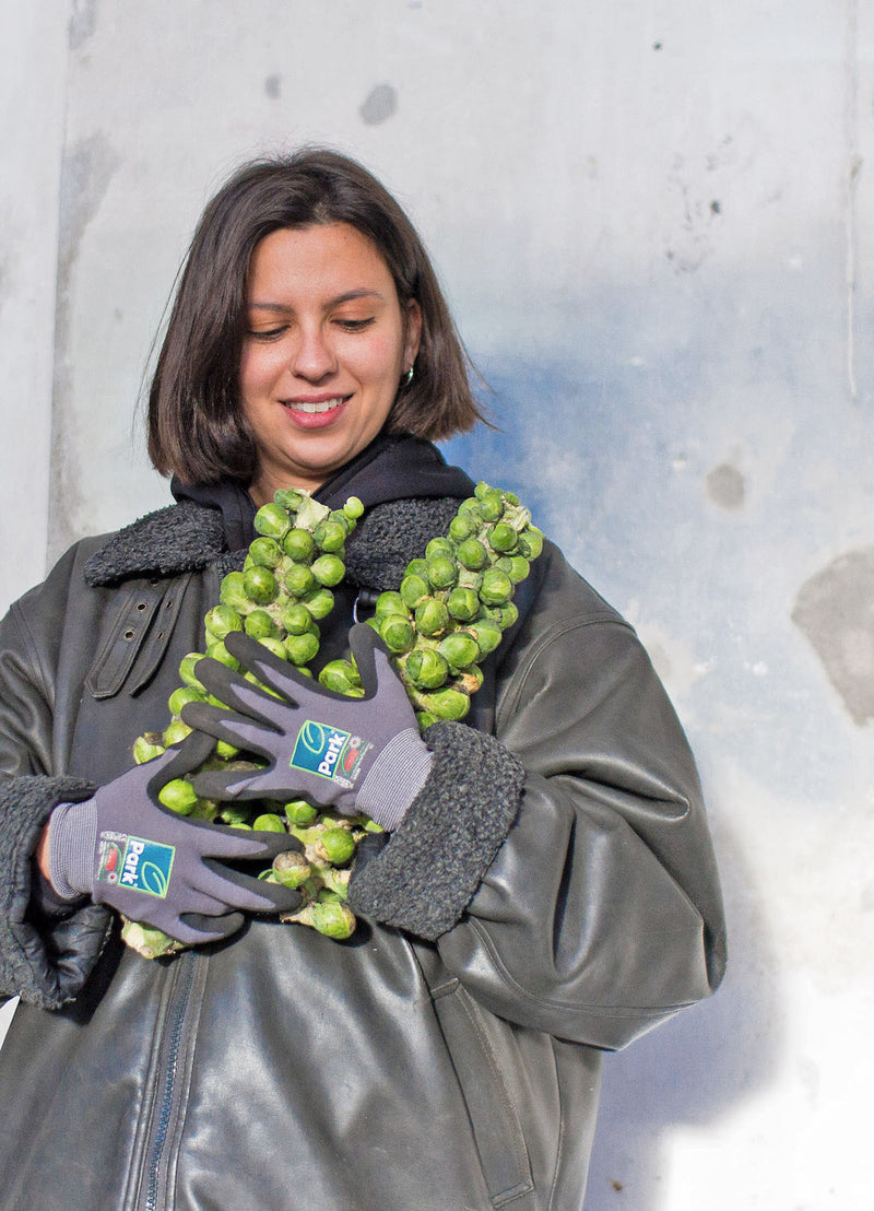 A GRIM volunteer holding stalks of brussels sprouts