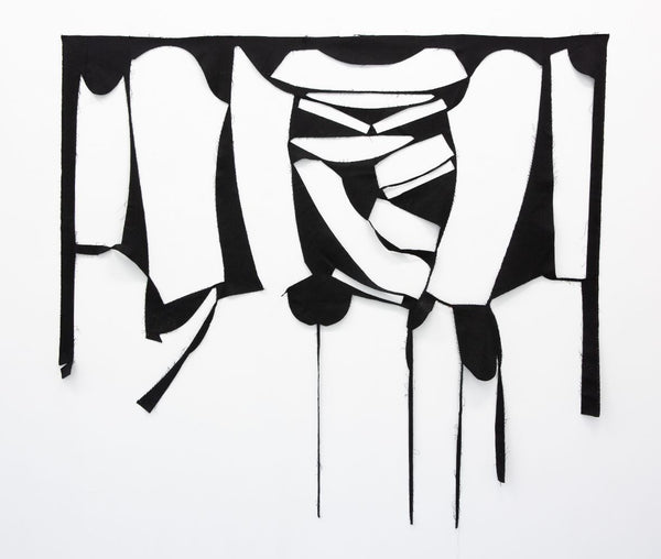 artwork made of fabric with cut outs from cutting a garment. negative of a garment