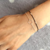 Wrist wearing black silk bracelet with silver wire