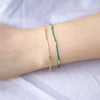 Wrist wearing green silk bracelet with gold wire