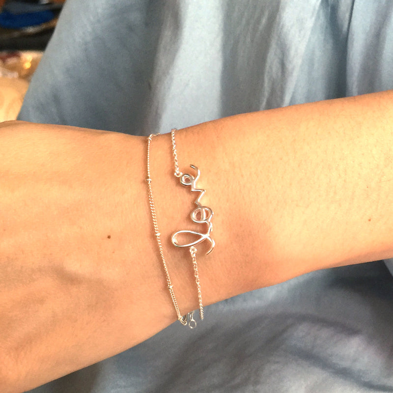 Wrist wearing gold ball chain bracelet